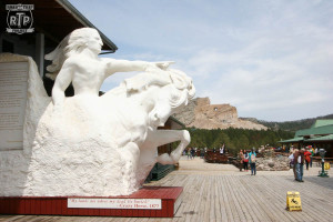 A scale model of the completed Crazy Horse monument with the real thing in the background.